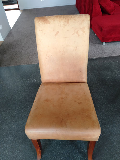 Faded stained leather chair